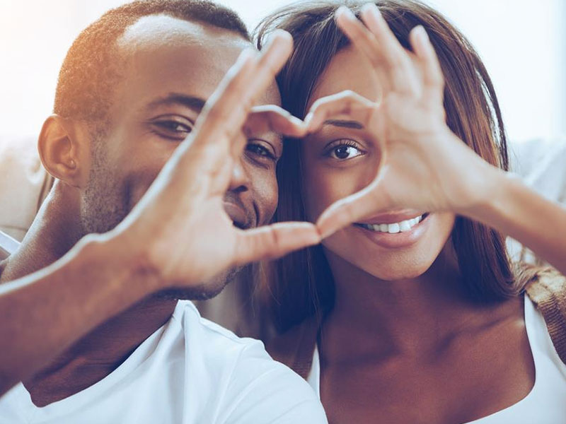 A couple who has strong emotional attraction and physical attraction, smiling and making a heart shape out of their hands.
