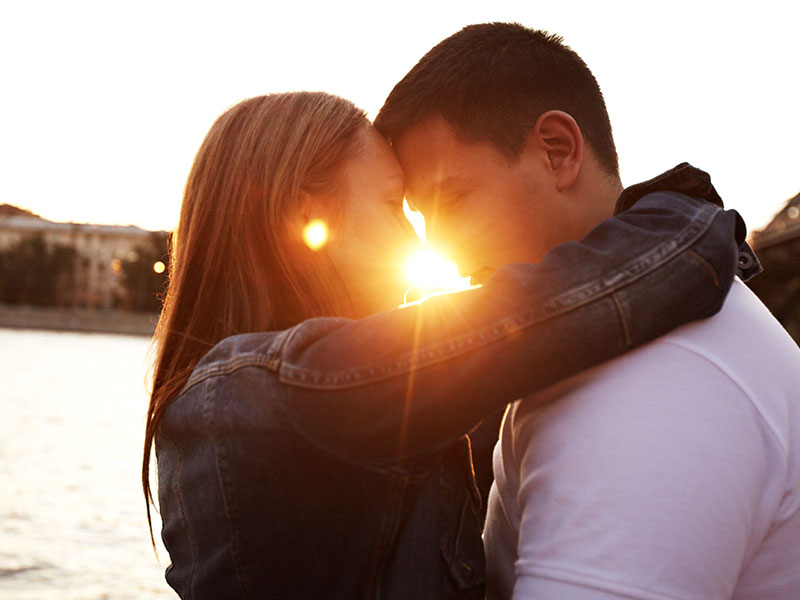 A couple in a love hate relationship kissing in front of the sunset.