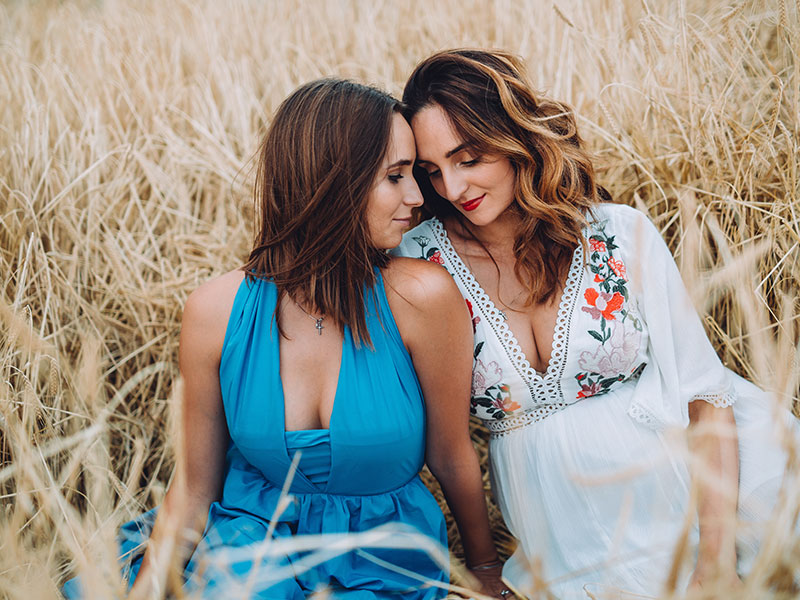Two women who strive to exemplify selfless love, leaning into each other in a field and smiling during their engagement photoshoot.