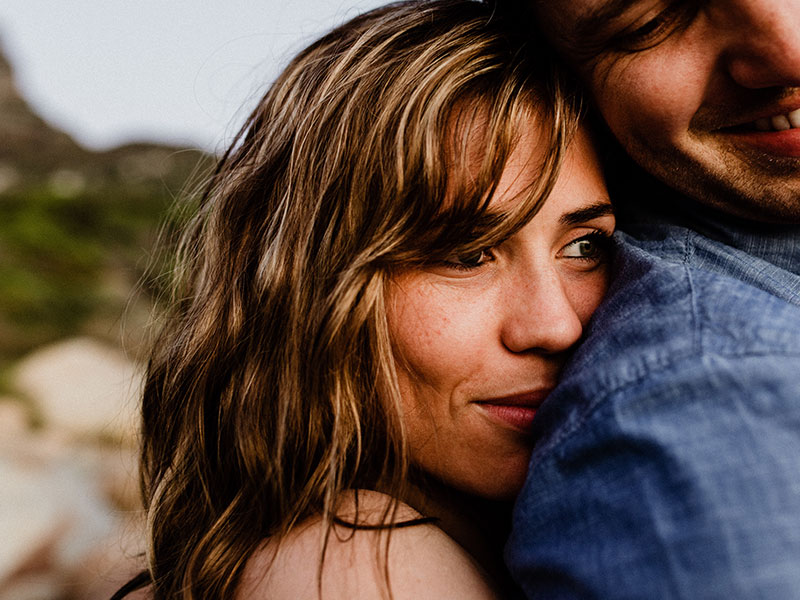 A woman who's a serial monogamist hugging her boyfriend tightly on the beach.