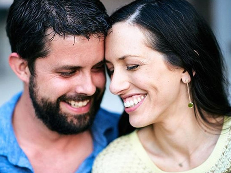 A couple in a serious relationship smiling and laughing with each other.